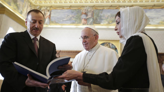 Pope Francis exchanges gifts with the President of Azerbaijan Ilham Aliyev, left, and his wife Mehriban Aliyeva, right, during a private audience at the Vatican, Friday, March 6, 2015. (AP Photo/Max Rossi, Pool)