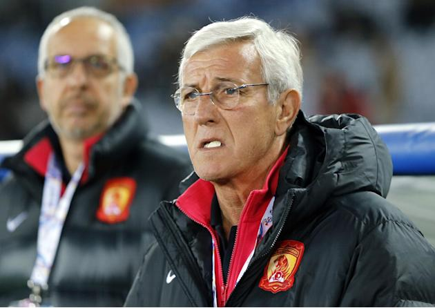 Guangzhou Evergrande coach Marcello Lippi, right, waits for the start of his team's match against Yokohama F. Marinos during their group stage soccer match of the AFC Champions League in Yokohama,
