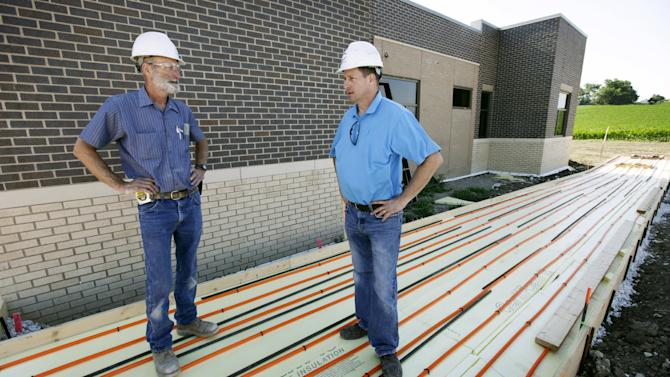 """In this Tuesday, June 19, 2012 photo, electrical contractor Howie Drees talks with foreman Don Irlbeck, left, on a job site in Carroll, Iowa. """"I would say Obama and his staff stepped up and made some tough decisions and put some money out there and kept things moving,"""" says Drees, who says up half the projects he's worked on in recent years involved federal funds. """"I was happy to see someone actually try to stimulate the economy with low interest rates, instead of waiting until more damage was done."""" (AP Photo/Charlie Neibergall)"""