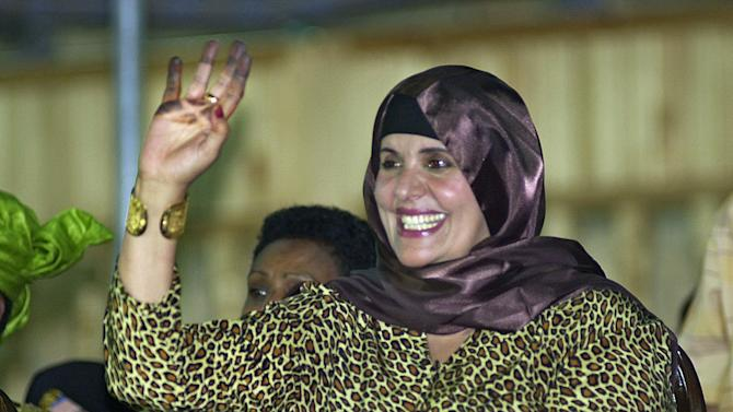 FILE - In this Monday, Sept. 1, 2003 file photo, showing Safiya Gadhafi, the wife of Libyan leader Moammar Gadhafi, waves at Libyan soldiers during a military parade at Tripoli's main square.  Ousted Libyan leader Moammar Gadhafi's wife and other relatives fled to Algeria Monday, the Algerian foreign ministry said, declaring that Gadhafi's wife, daughter, two of his sons and their children entered the neighboring country on Monday. It did not say whether Moammar Gadhafi himself was with the family group. (AP Photo/Amr Nabil, File)