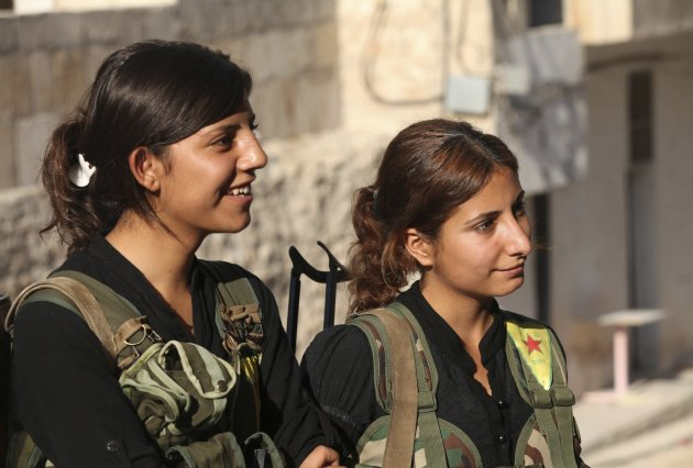 Kurdish fighters from the YPG stand along a street in Aleppo's Sheikh Maqsoud neighborhood