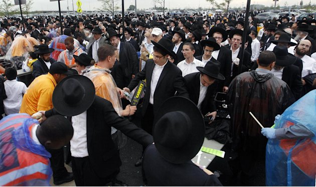 A large crowd of Orthodox Jewish men wait to be checked by security at MetLife stadium in East Rutherford, N.J, Wednesday, Aug. 1, 2012, as they arrive for the start of the celebration Siyum HaShas. T