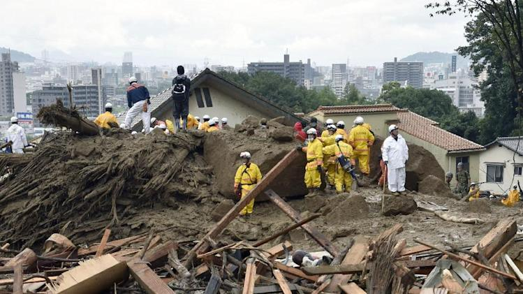 Debris of houses and trees cover a residential area as rescuers search for missing people following a massive landslide in Hiroshima, western Japan, Friday, Aug. 22, 2014. Heavy rain showers forecast are raising the risks of further landslides in Hiroshima, hindering efforts to locate the dozens of people missing after hills in several areas collapsed earlier this week. (AP Photo/Kyodo News) JAPAN OUT