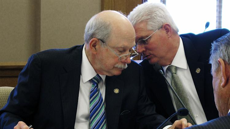 Kansas state Sens. Les Donovan, left, a Wichita Republican, and Pat Apple, right, a Louisburg Repubilcan, confer during negotiations with House members over tax cuts, Thursday, April 26, 2012, at the Statehouse, in Topeka, Kan. (AP Photo/John Hanna)