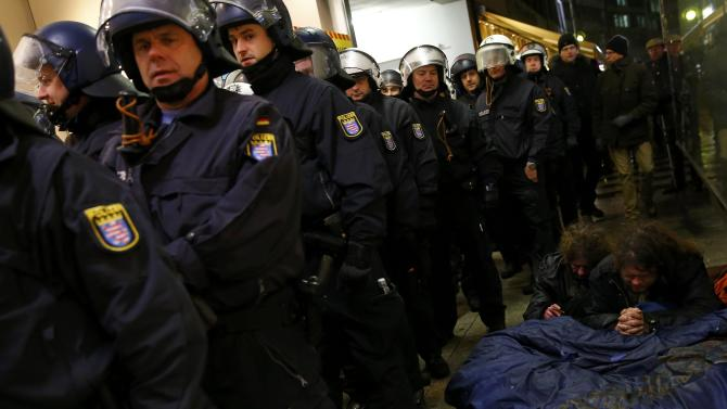 German riot police officers line up next to a couple of homeless people as they watch opponents of the movement of Patriotic Europeans Against the Islamisation of the West (PEGIDA) demonstrating against PEGIDA in Frankfurt