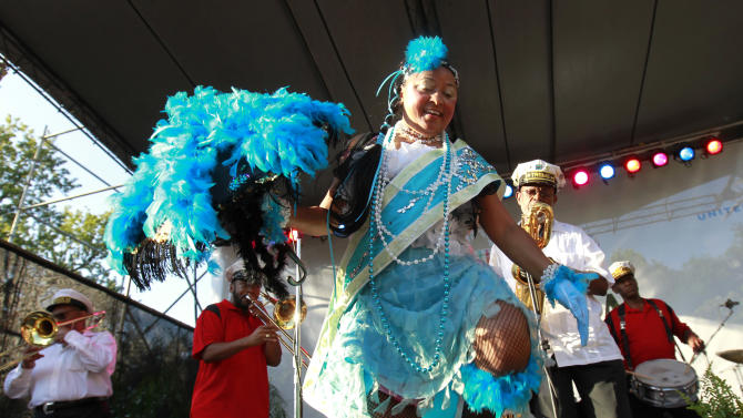 Jennifer Jones dances with the Treme Brass band at a sunrise concert marking International Jazz Day in New Orleans, Monday, April 30, 2012. The performance, at Congo Square near the French Quarter, is one of two in the United States that day; the other is in the evening in New York. Thousands of people across the globe are expected to participate in International Jazz Day, including events in Belgium, France, Brazil, Algeria and Russia. (AP Photo/Gerald Herbert)