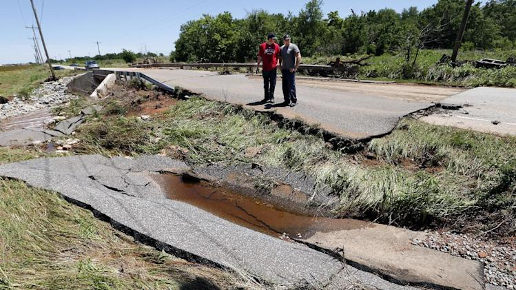 Two Navy veterans revisit the washed out roadway west of Sara Road on SW 29th Street where they rescued a woman and her daughter from a flooded car during Friday night's storm, Saturday, June 1, 2013 in Oklahoma City.. (AP Photo/The Oklahoman, Steve Sisney) LOCAL STATIONS OUT (KFOR, KOCO, KWTV, KOKH, KAUT OUT); LOCAL WEBSITES OUT; LOCAL PRINT OUT (EDMOND SUN OUT, OKLAHOMA GAZETTE OUT) TABLOIDS OUT