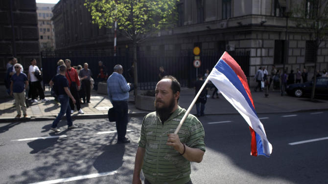 """A man holds a Serbian flag during a demo in Belgrade, Serbia, Monday, April 22, 2013. Thousands of Serb demonstrators, chanting """"Treason, Treason,"""" protested on Monday against an agreement to normalize relations with breakaway Kosovo, the potentially landmark deal that could end years of tensions between the Balkan rivals and put them on a path to European Union membership. (AP Photo/ Marko Drobnjakovic)"""