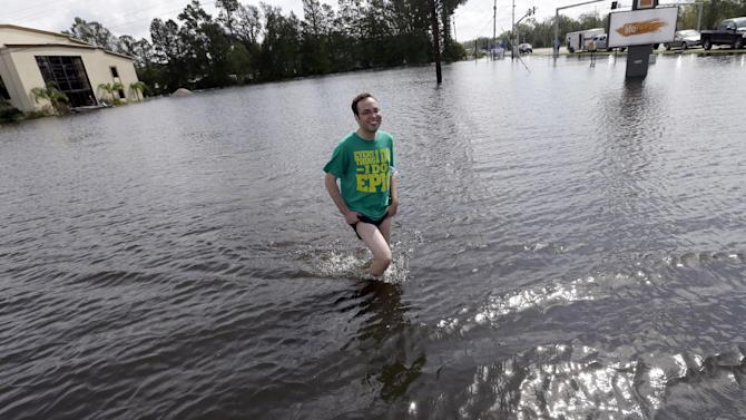 Christopher Keller walks through floodwaters in the aftermath of Hurricane Isaac in Reserve, La., Saturday, Sept. 1, 2012. Floodwaters cover many streets and power remains out in some areas. Louisiana's Public Service Commission said more than 443,000 customers remained without electricity around Louisiana on Saturday morning, days after Hurricane Isaac crept across the state. (AP Photo/David J. Phillip)