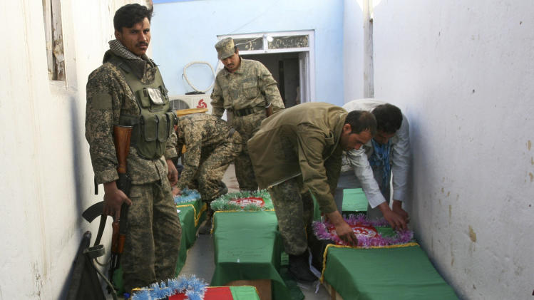 FILE - In this Wednesday, April 17, 2013 file photo, Afghan Army soldiers prepare the coffins for their killed comrades in the morgue of the main hospital in Ghazni, Afghanistan after a roadside bomb killed the five soldiers who were part of a government security force guarding a convoy of trucks in Ghazni's Qarabagh district. The Taliban have announced they will launch their spring offensive on Sunday, April 28, 2013, signaling plans to step up attacks as the weather warms across Afghanistan, making both travel and fighting easier.(AP Photo/Rahmatullah Nikzad, File)