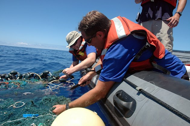 File - In this Aug. 11, 2009 file photo provided by the Scripps Institution of Oceanography shows Matt Durham, center, pulling in a large patch of sea garbage with the help of Miriam Goldstein, right,