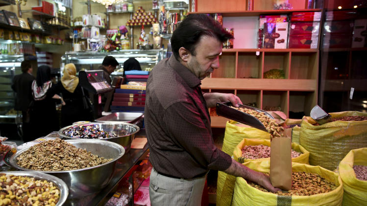 In this Sunday, March 31, 2013 photo, an Iranian shopkeeper sells pistachios, at his shop in western Tehran, Iran. Pistachios are Iran's top non-oil export and provide work for hundreds of thousands of people. Still, Iranian authorities are backing the boycott. They laud it as a way to decrease domestic pistachio consumption and leave more nuts for exporting, which has become an increasingly important pipeline for foreign revenue as sanctions squeeze Iran's oil and gas sales. (AP Photo/Ebrahim Noroozi)