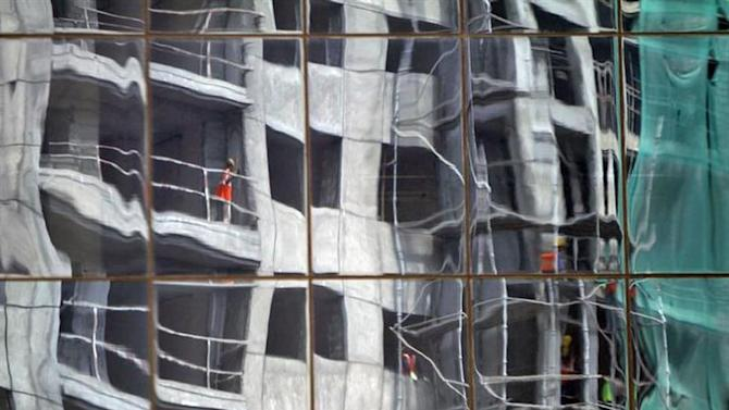 A residential building undergoing construction is reflected on the glass facades of a commercial complex in the southern Indian city of Chennai September 30, 2013.
