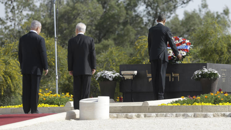 U.S. President Barack Obama, right, with Israeli President Shimon Perez, center, and Israeli Prime Minister Benjamin Netanyahu stand behind, lays a wreath at the grave of Theodor Herzl during his visit to Mt. Herzl in Jerusalem, Israel, Friday, March 22, 2013. (AP Photo/Pablo Martinez Monsivais)
