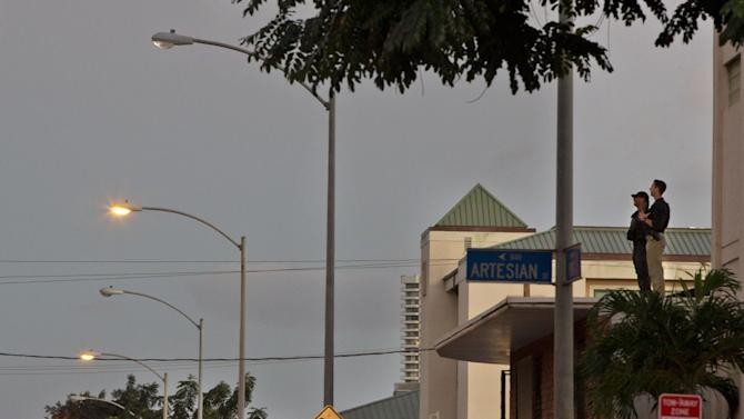 Secret Service agents keep watch from the roof by Alan Wong's Restaurant where President Barack Obama and first lady Michelle Obama had dinner, Saturday, Dec. 27, 2014, in Honolulu, Hawaii during the Obama family vacation. (AP Photo/Jacquelyn Martin)