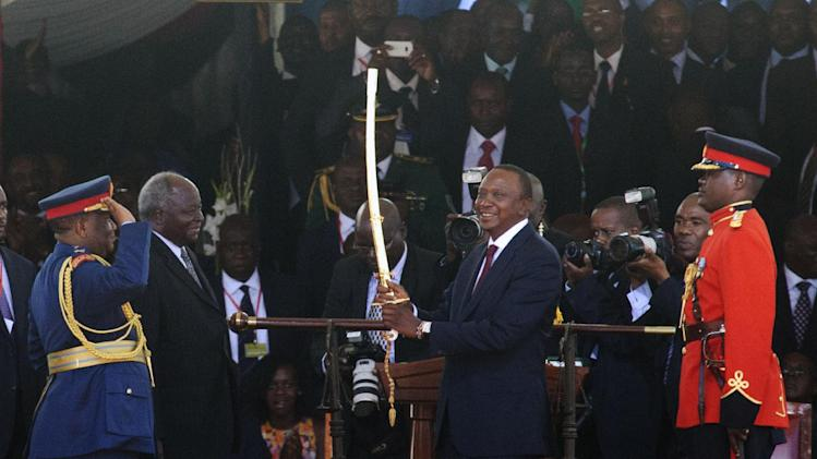 President Uhuru Kenyatta, right, receives the sword of the Commander In Chief of the Kenya Armed Forces from outgoing president Mwai Kibaki, second left, at Moi International Sports Complex in Nairobi, Kenya Tuesday, April 9, 2013, watched by Julius Karangi, Chief of Defence Forces Kenya, left. Uhuru Kenyatta was sworn in as the Kenya's fourth president Tuesday in a stadium filled with tens of thousands of Kenyans and a dozen African leaders. (AP Photo/Sayuyid Azim)