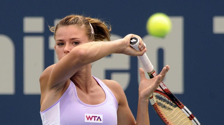 Camila Giorgi, of Italy, watches her forehand during her 6-2, 6-4 semifinal loss to Magdalena Rybarikova, of Slovakia, at the New Haven Open tennis tournament in New Haven, Conn., on Friday, Aug. 22, 2014. (AP Photo/Fred Beckham)