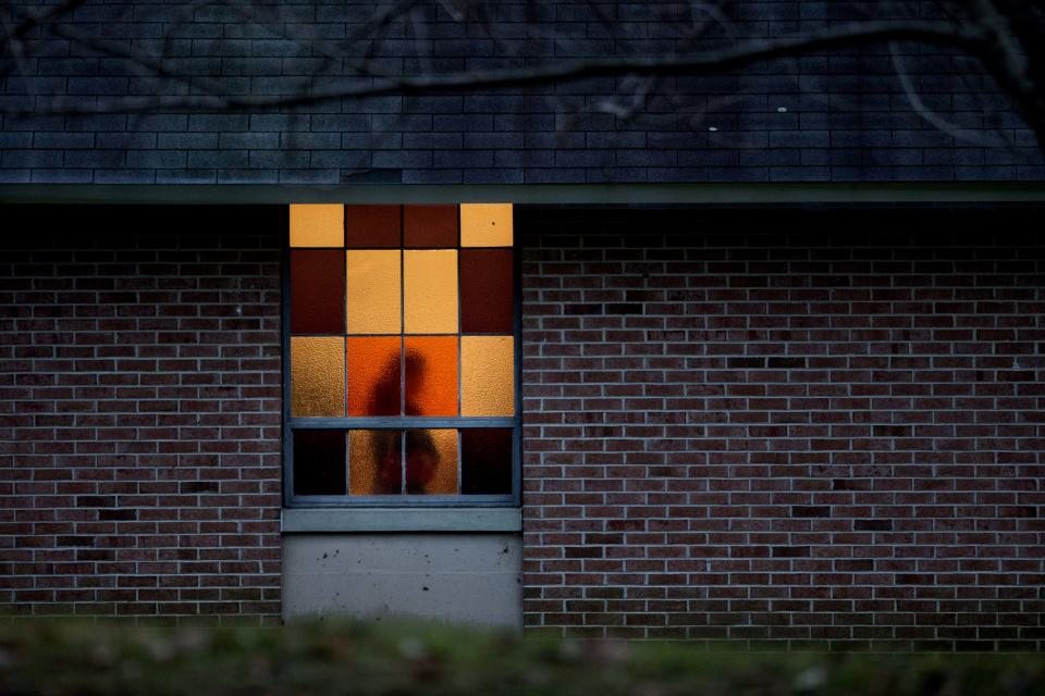 A mourner passes a stain glassed window while paying her respects during the wake for Sandy Hook Elementary School shooting victim Charlotte Helen Bacon, 6, at Christ the King Lutheran Church, Tuesday, Dec. 18, 2012, in Newtown, Conn. (AP Photo/David Goldman)