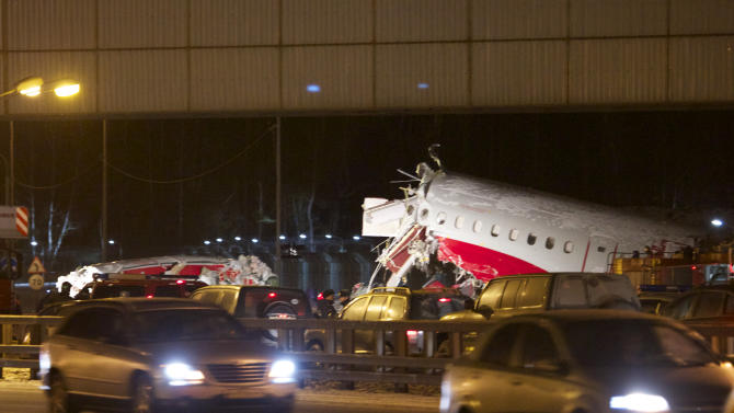 Cars travel past the wreckage of a plane that careered off the runway at Vnukovo Airport in Moscow, Saturday, Dec. 29, 2012. A Tu-204 aircraft belonging to Russian airline Red Wings careered off the runway at Russia's third-busiest airport on Saturday, broke into pieces and caught fire, killing several people. (AP Photo/Ivan Sekretarev)