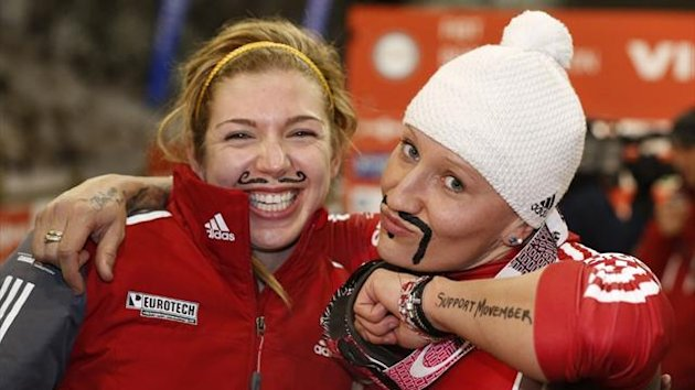 Kaillie Humphries (R) and Chelsea Valios of Canada show off their painted on moustaches after they finished first in the FIBT women's bobsled World Cup race in Park City (AFP)