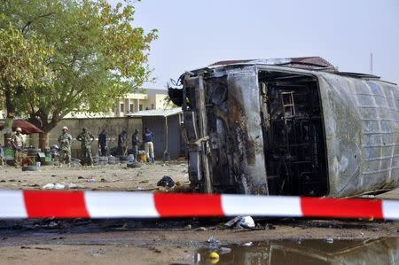 Soldiers are seen at the scene of a suicide bombing at a bus station in Kano