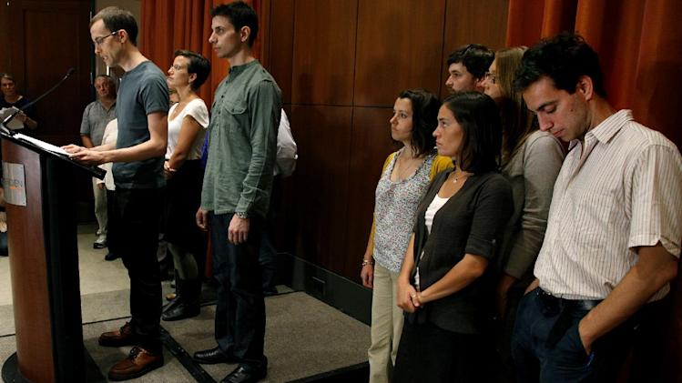 Alex Fattal, right, bows his head as he listens to freed American Shane Bauer, left, as he addresses reporters along with Josh Fattal, center left, who was released with him, Sunday, Sept. 25, 2011 in New York. The two men were released last week after being held for espionage in an Iranian jail for almost two years. (AP Photo/Craig Ruttle)