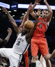 Brooklyn Nets forward Reggie Evans (30) loses the ball as Toronto Raptors guard Jose Calderon (8) defends in the first half of an NBA basketball game Tuesday, Jan. 15, 2013, in New York. (AP Photo/Kathy Willens)