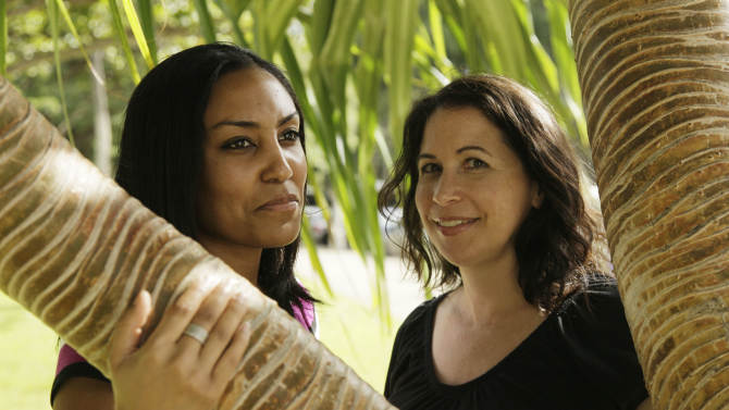 Taeko Bufford, left, and Diane Cervelli, right, pose near Waikiki beach in Honolulu, Monday, Dec. 19, 2011. The two Southern California women filed a lawsuit Monday against a Hawaii bed and breakfast, saying the business denied them a room because they are gay.  (AP Photo/Eric Risberg)