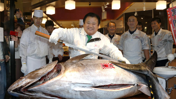 Sushi restauranteur Kiyoshi Kimura poses with a 507-pound (230-kilogram) bluefin tuna he bought at an auction before cutting it at his restaurant near Tsukiji fish market in Tokyo, Sunday, Jan. 5, 2014. Kimura paid 7.36 million yen (about $70,000) for the bluefin tuna in the year's celebratory first auction, just one-twentieth of what he paid a year earlier despite signs the species is in serious decline. (AP Photo/Shizuo Kambayashi)