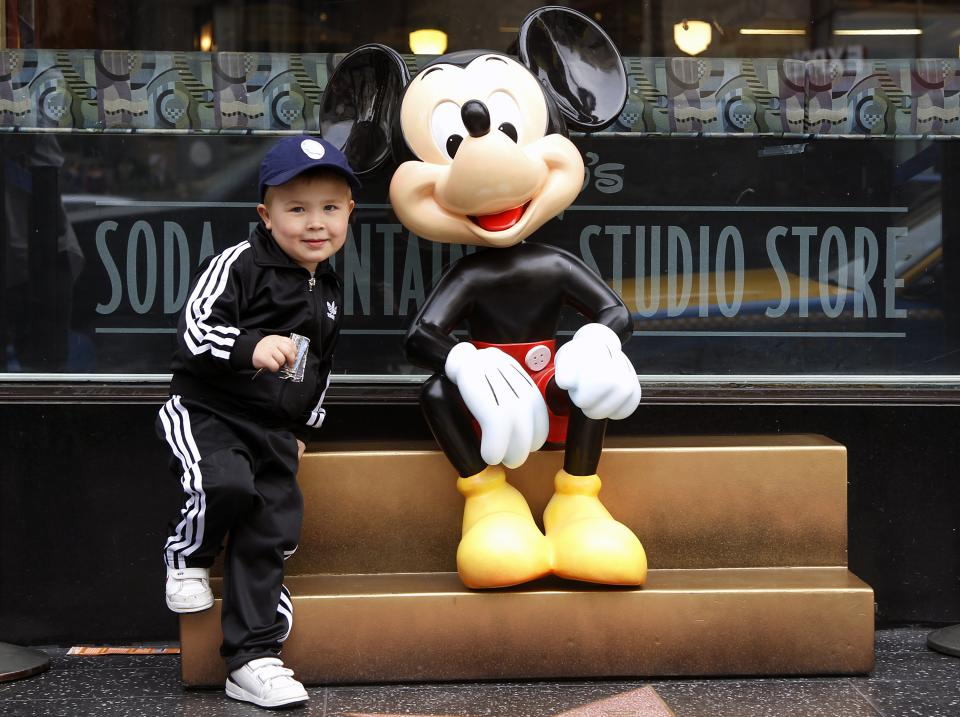 In this Feb. 6, 2012 photo, Ruben Castensson, from Stockholm, Sweden, poses with Mickey Mouse at The Disney Soda Fountain & Studio Store on Hollywood Boulevard in Los Angeles. Walt Disney Co. releases quarterly financial earnings Tuesday, Feb. 7, 2012, after the market close. (AP Photo/Damian Dovarganes)
