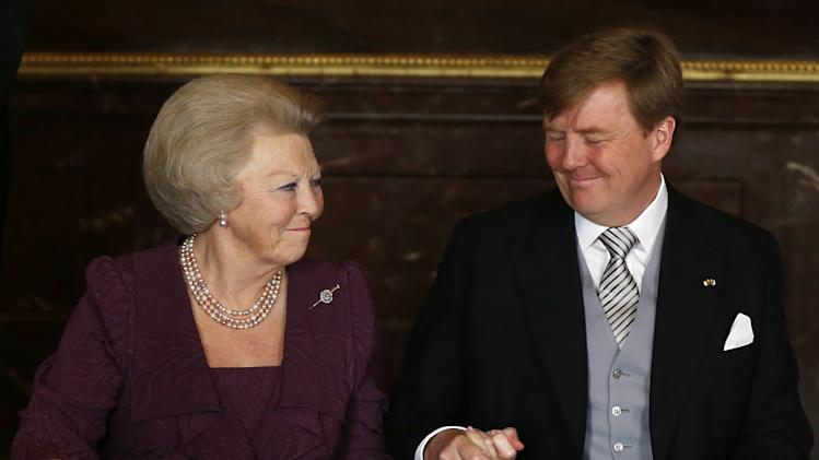 Dutch Princess Beatrix, left, clasps the hand of her son, King Willem-Alexander, after the Act of Abdication was signed to end her reign as Monarch, in the Mozeszaal or Mozes hall of the Royal Palace in Amsterdam, The Netherlands, Tuesday April 30, 2013. Around a million people are expected to descend on the Dutch capital for a huge street party to celebrate the first new Dutch monarch in 33 years. (AP Photo/Bart Maat, pool)