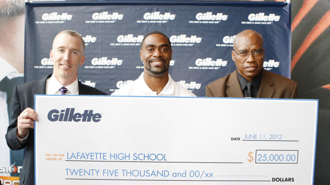 COMMERCIAL IMAGE - American 100m record holder Tyson Gay, center, poses for photo with Phil Ryan, Brand Community Manager of Gillette, left, after presenting his former high school coach Ken Northington, right, with a $25,000 Great Start grant to support the next generation of men at Gillette World Shaving Headquarters, Monday, June 11, 2012, in Boston.  The grant will support the track and field team at Lafayette High School in Lexington, KY., where Gay got his great start. (Photo by Bizuayehu Tesfaye/Invision for Gillette/AP Images)