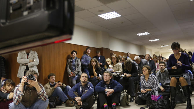 Media watch a TV screen in a hall outside a court room of the Moscow City Court where three members of the punk band Pussy Riot are set to make their case before a Russian appeals court that they should not be imprisoned, in Moscow, Wednesday. Oct. 10, 2012.  Their impromptu performance inside Moscow's main cathedral in February came shortly before Putin was elected to a third term. The three women were convicted in August of hooliganism motivated by religious hatred and sentenced to two years in prison. (AP Photo/Sergey Ponomarev)