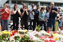 People in front of the Olympia Einkaufszentrum shopping centre in Munich mourn those killed there in a shooting rampage