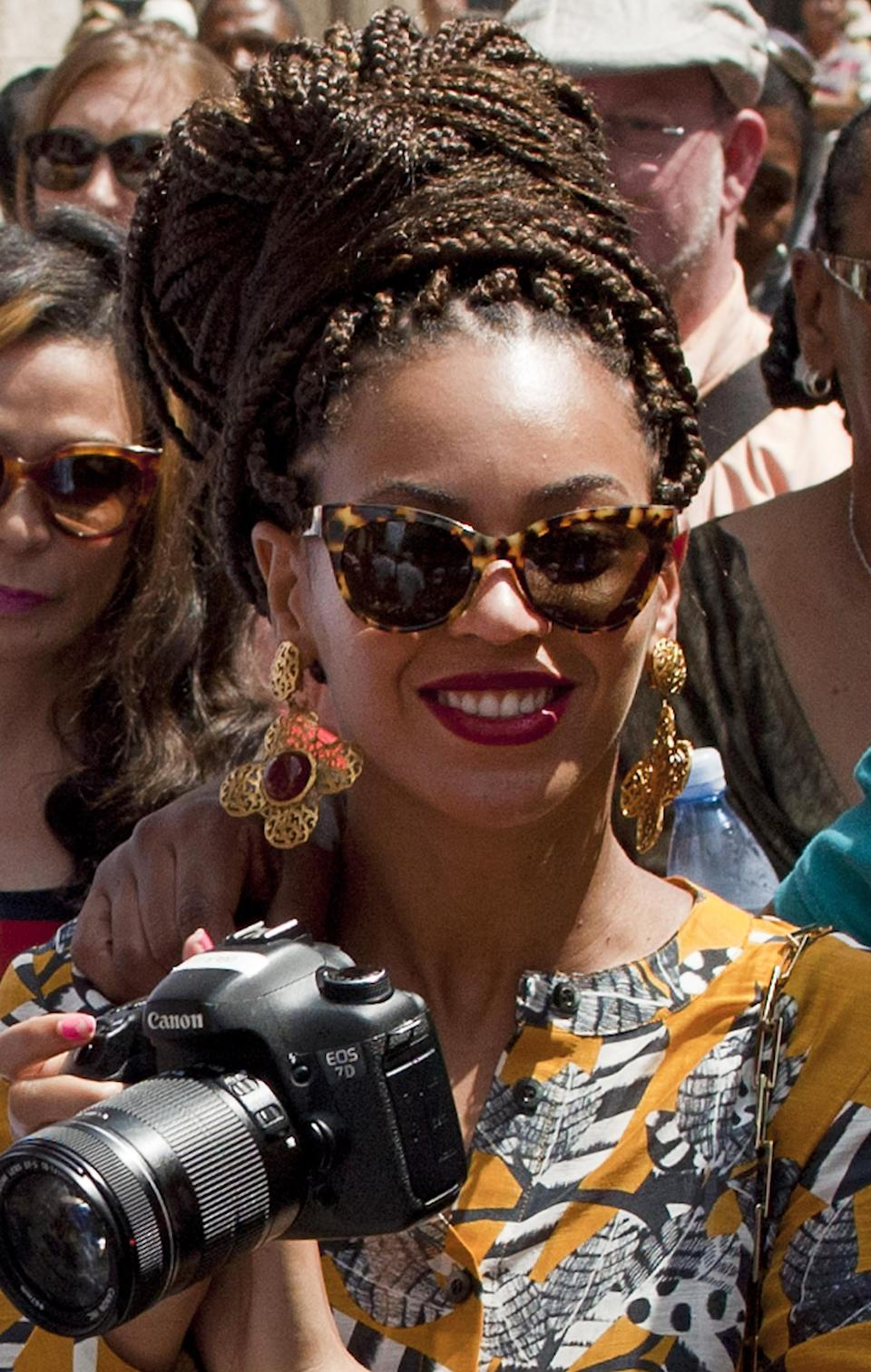 U.S. singer Beyonce holds her camera as she tours Old Havana, Cuba, Thursday, April 4, 2013. Beyonce is in Havana with her husband, rapper Jay-Z, on their fifth wedding anniversary. (AP Photo/Ramon Espinosa)