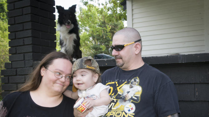 Kaiba Gionfriddo is hugged by his parents April and Bryan outside their Youngstown, Ohio home Tuesday, May 21, 2013. Born with a birth defect that caused the boy to stop breathing every day, he can now breathe normally, with a first-of-a-kind biodegradable airway made by Michigan doctors using plastic particles and a 3-D laser printer. (AP Photo/Mark Stahl)