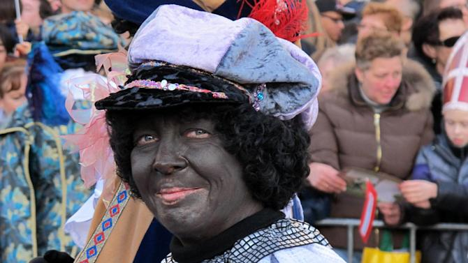 """In this photo taken Sunday, Nov. 18, 2012 a person dressed as """"Zwarte Piet"""" or """"Black Pete"""" attend a parade after St. Nicholas, or Sinterklaas, arrived by boat in Amsterdam, Netherlands. Foreigners visiting the Netherlands in winter are often surprised to see that the Dutch version of St. Nicholas' little helpers resemble a racist caricature of a black person. The overwhelming majority of Dutch, who pride themselves on tolerance, are fiercely devoted to their holiday tradition and say """"Zwarte Piet"""", whose name means """"Black Pete"""", is absolutely harmless, a fictional figure who does not represent any race. But now a growing group of Dutch natives are questioning whether this particular part of the tradition should be changed. (AP Photo/ Margriet Faber)"""