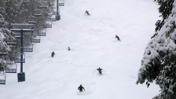 FILE- In this Monday, Jan. 18, 2010 file photo, a group of skiers and snowboarders make first tracks in the fresh snow at Pats Peak ski area in Henniker, N.H.  The relationship between skiers and snowboarders might still be a bit icy at times, but a versatile group has discovered there's more than one way to get down the mountain.     (AP Photo/Jim Cole, FILE)