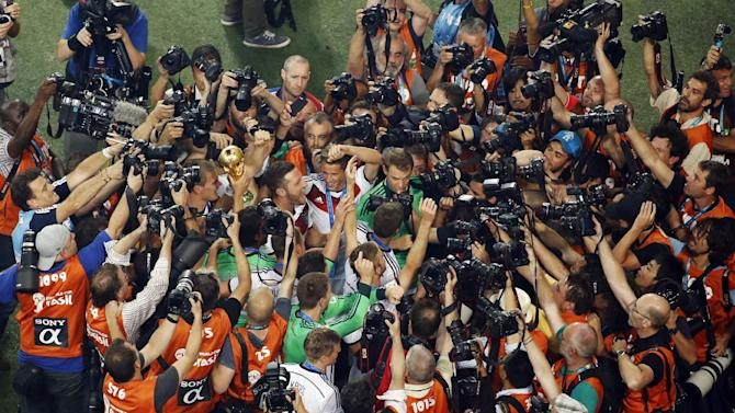 German players are mobbed by media after winning the World Cup final soccer match between Germany and Argentina at the Maracana Stadium in Rio de Janeiro, Brazil, Sunday, July 13, 2014. Mario Goetze volleyed in the winning goal in extra time to give Germany its fourth World Cup title with a 1-0 victory over Argentina on Sunday