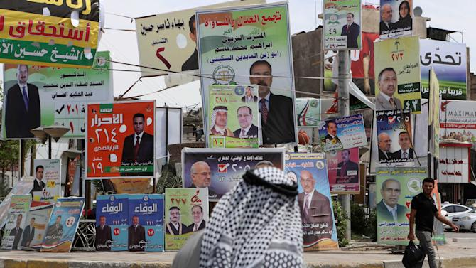 In this photo taken on April 15, 2014, Iraqis past election campaign posters in Basra, Iraq. The vibrant posters promise jobs, prosperity and security coming from Iraq's first parliamentary elections since U.S. troops withdrew from the country, but so far, voters have only dim hopes as sectarian bloodshed rages unstopped. (AP Photo/Nabil al-Jurani)