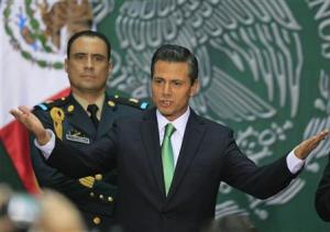Mexico's President Pena Nieto gestures before he signs into law a radical reform of the country's energy, at the National Palace in Mexico City