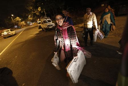 Polling officers carry EVM as they leave a polling station at the end of polls, during the state assembly election in New Delhi