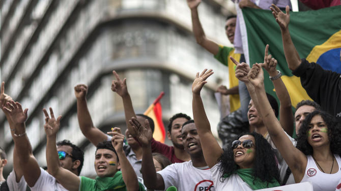 People shout anti-government slogans during a protest in Belo Horizonte, Brazil, Saturday, June 22, 2013. Demonstrators once again took to the streets of Brazil on Saturday, continuing a wave of protests that have shaken the nation and pushed the government to promise a crackdown on corruption and greater spending on social services. (AP Photo/Felipe Dana)