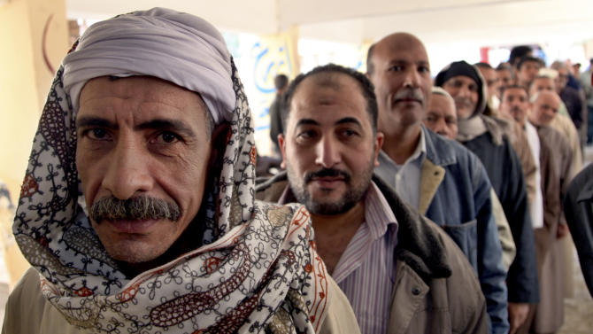 Egyptian men line up outside a polling station to cast their votes during a referendum on a disputed constitution drafted by Islamist supporters of President Morsi in Cairo, Egypt, Saturday, Dec. 15, 2012. (AP Photo/Khalil Hamra)