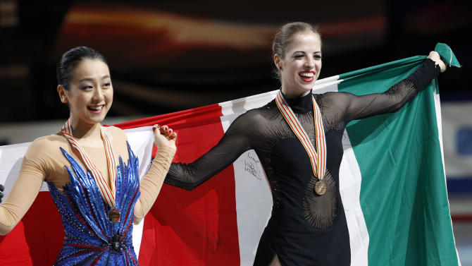 Gold medalist Mao Asada, left, of Japan and bronze medalist Carolina Kostner, right, of Italy pose for photographers with their national flag during an awarding ceremony of the women's figure skating event of the World Figure Skating Championships in Saitama near Tokyo, Saturday, March 29, 2014. (AP Photo/Koji Sasahara)