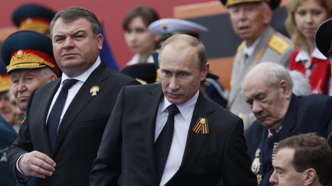 FILE - In this Wednesday, May 9, 2012 file photo, Russia's Defense Minister Anatoly Serdyukov, left, Russian President Vladimir Putin, center, and Prime Minister Dmitry Medvedev, bottom right, watch the Victory Day Parade, in Moscow. Russian President Vladimir Putin has fired the country's defense minister two weeks after a criminal probe was opened into alleged fraud in the sell-off of military assets. Putin made the announcement of Anatoly Serdyukov's dismissal on Tuesday Nov. 6, 2012 in a meeting with Moscow regional governor Sergei Shoigu, whom he appointed as the new minister. (AP Photo/Alexander Zemlianichenko)