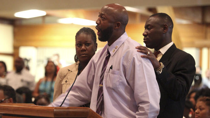 Tracy Martin, center, speaks at the Sanford City Commission meeting with Trayvon's mother, Sybrina Fulton, left, and the family lawyer, Benjamin Crump at the Sanford Civic Center in Sanford Fla., Monday, March 26, 2012. Martin, a black teen, was fatally shot by a neighborhood watch captain last month. (AP Photo/Julie Fletcher)