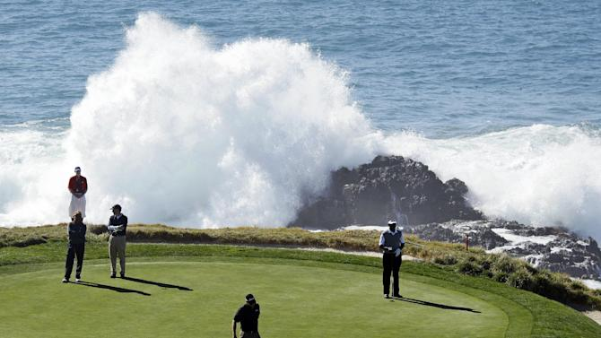Tom Gillis prepares to putt on the seventh green of the Pebble Beach Golf Links as playing partner Vijay Singh, right, looks on during the first round of the Pebble Beach National Pro-Am PGA Tour golf tournament in Pebble Beach, Calif., Thursday, Feb. 9, 2012. (AP Photo/Eric Risberg)