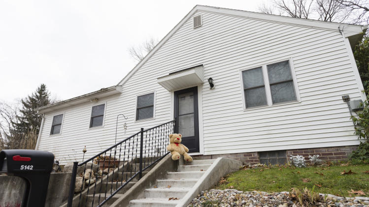 A lone teddy bear sits on the steps of the home in Toledo, Ohio, Tuesday Nov. 13, 2012.  Three children, their uncle, and their grandmother were found dead inside a garage at the house Monday in what appears to be a murder-suicide amid a custody dispute. (AP Photo/Rick Osentoski)