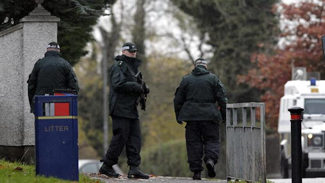 Police Service of Northern Ireland officers patrol the area close to a fatal shooting on the M1 motorway near Lurgan, Northern Ireland, Thursday, Nov. 1, 2012.  A veteran Northern Ireland prison officer was killed Thursday in a gun ambush as he was driving to work, the first slaying of a security-force member in the British territory in 18 months. Police said a gunman in a passing car shot David Black, 52, as he drove onto the M1 motorway southwest of Belfast. His car plummeted down a grassy embankment into a ditch.   (AP Photo/Peter Morrison)